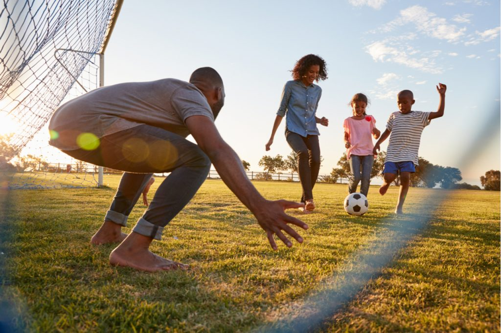 A boy kicks a football during a game with his family as part of the 9 tips for a safe, fun and healthier 4th of July celebration.