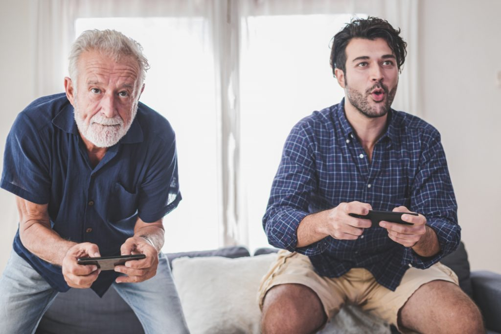 Father and son playing a video game together. One of the fun things to do at home.