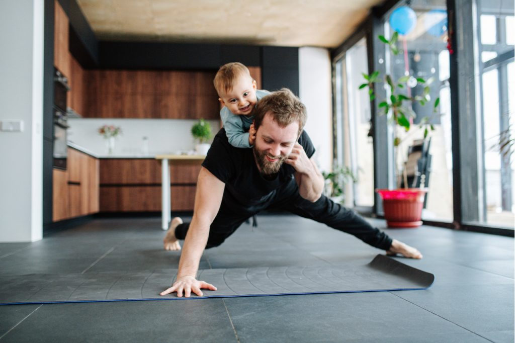A father doing some push-ups while giving his son a piggy back ride. What an active way to spend father's day in 2020.