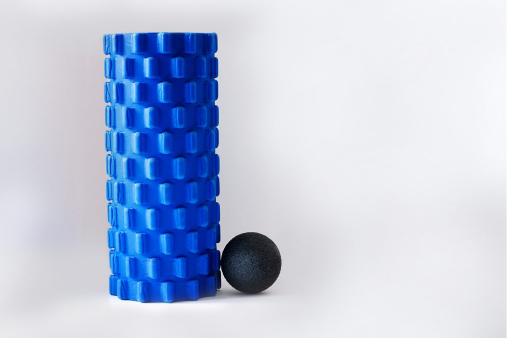 A blue foam roller right next to a black massage ball.