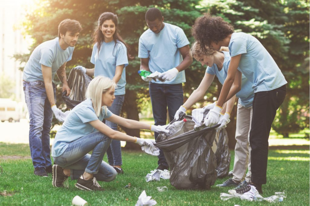 Young millennial volunteers picking garbage in park.