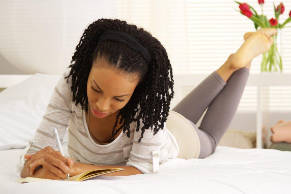 Woman in yoga wear writing in her journal.