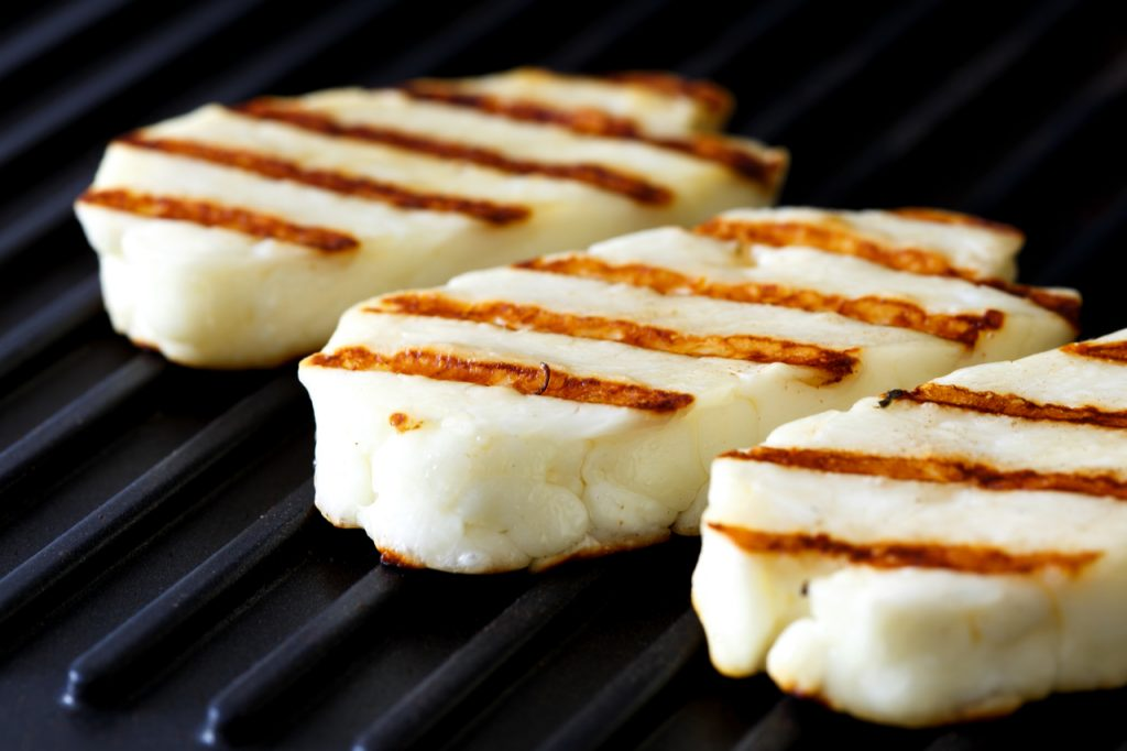 Three grilled slices of halloumi cheese on grill in perspective.