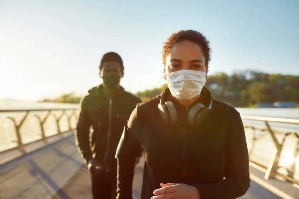Couple wearing face medical masks while running together on the bridge in the morning.