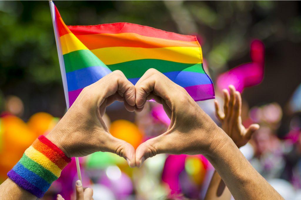 Hands forming a heart supporting pride and celebrating pride month with a rainbow flag in the background.