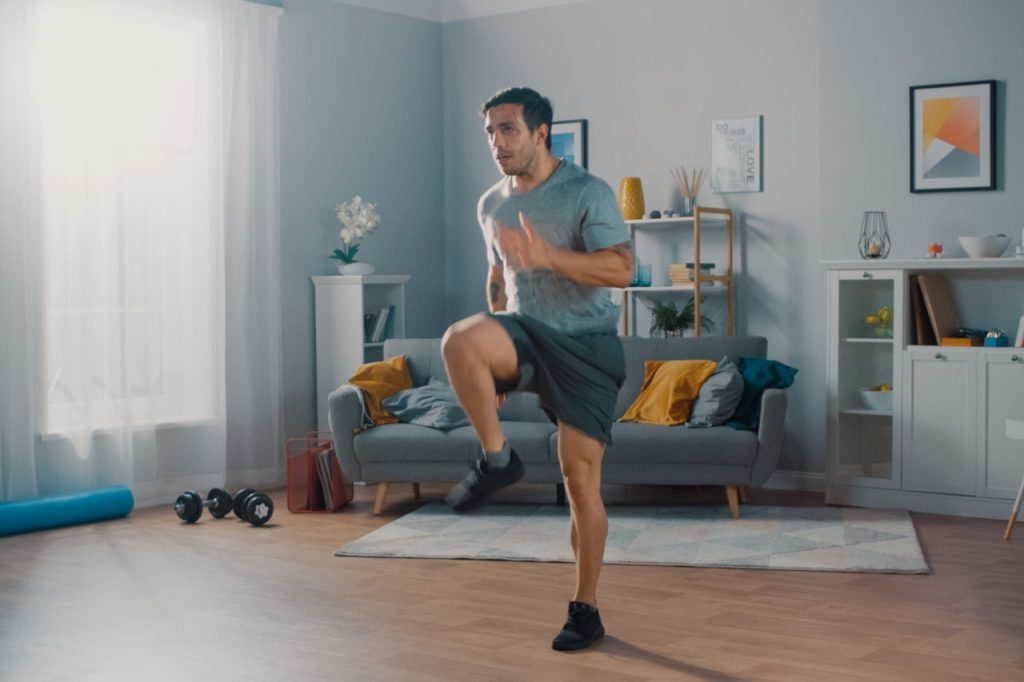 Man is energetically jogging in place at home.