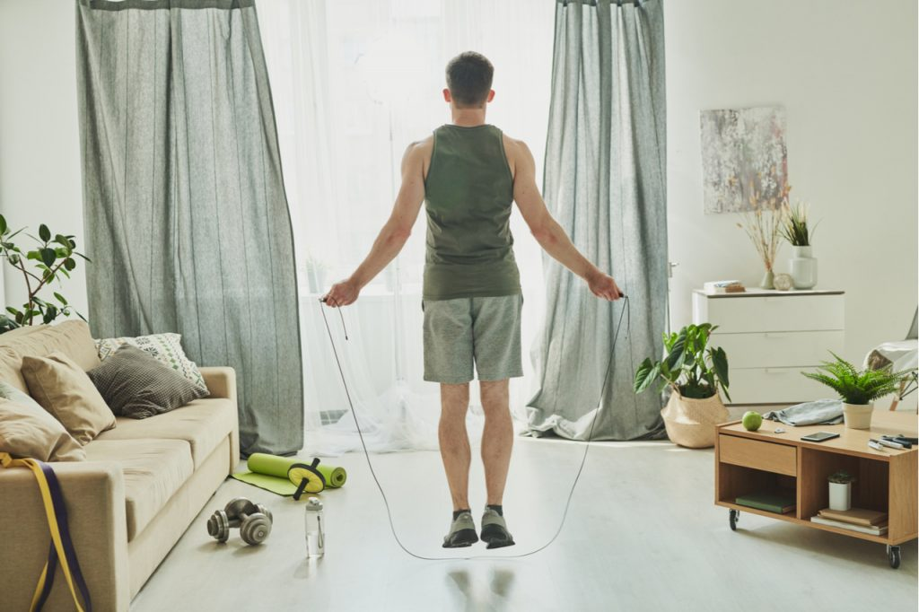Back view of young man skipping-rope in his living room is just one of the benefits of jumping rope.