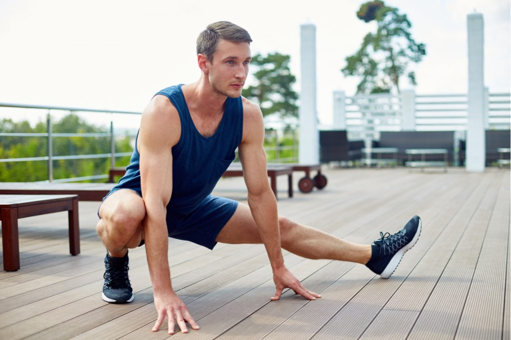 Sportsman doing side lunge while having training on spacious wooden terrace.