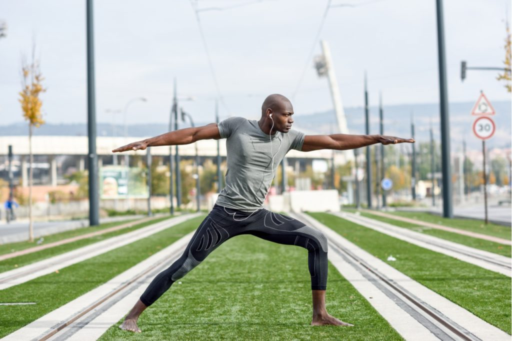 Man practicing yoga in urban background getting in control.