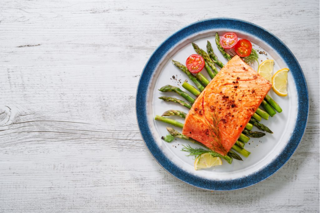 Grilled salmon garnished with green asparagus and tomatoes.