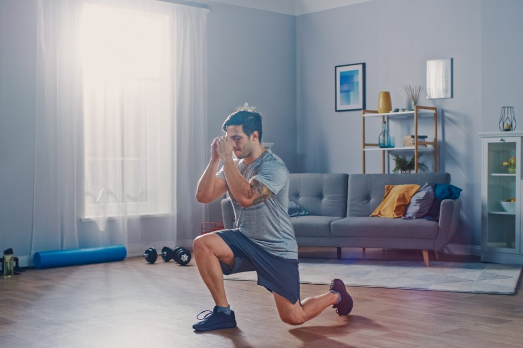 Strong athletic man doing forward lunge exercise at home.