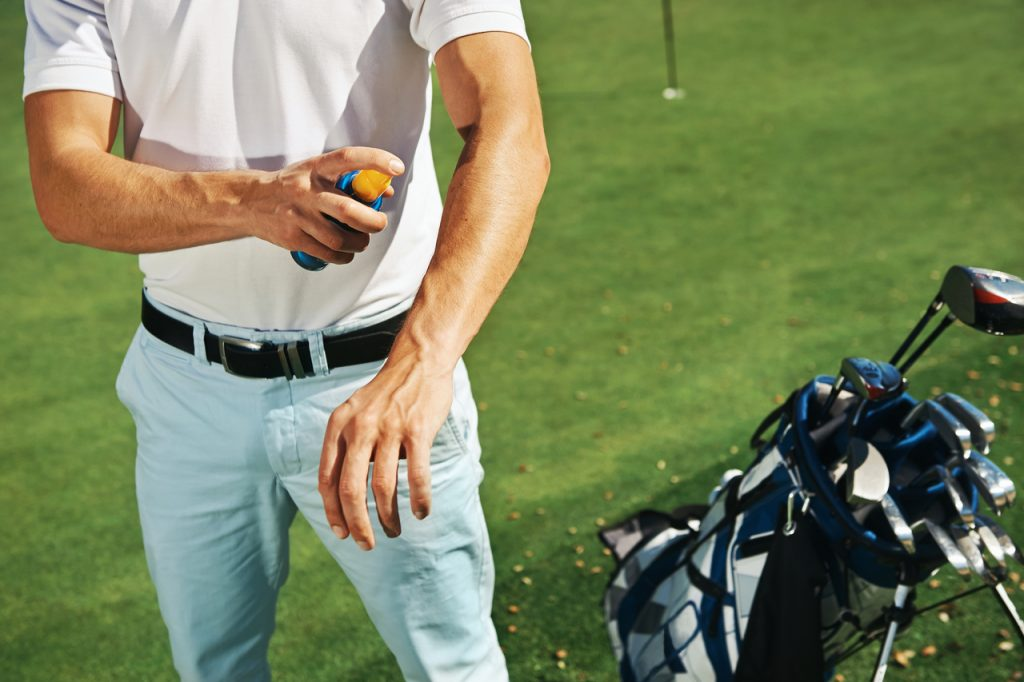 Golf sport man with sunblock lotion spray for spf protection.