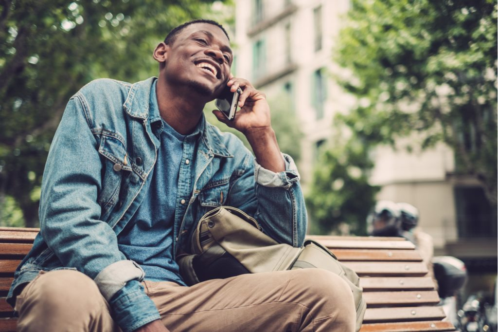 A man sitting on a bench at a park while happily talking to a friend on the phone.