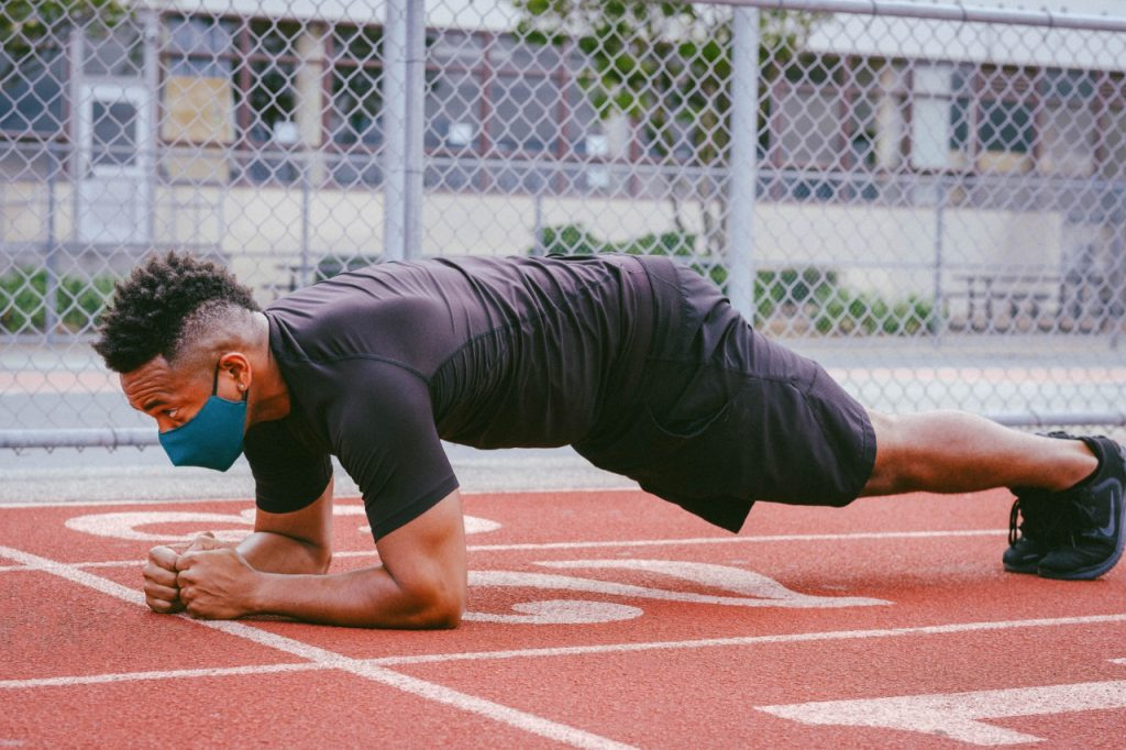 A man wearing a face mask doing planks on a running track.
