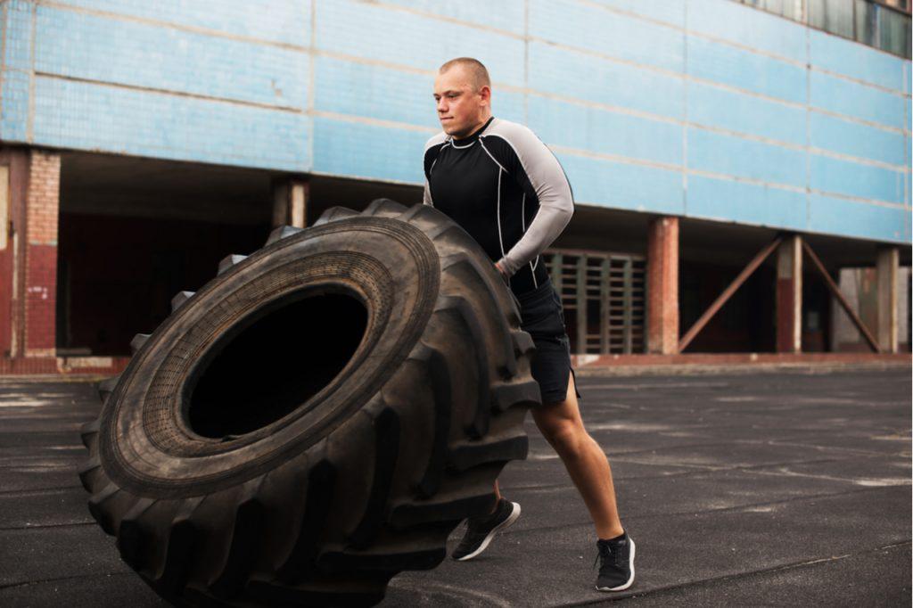 A man lifting a big tire as his Hero WODs