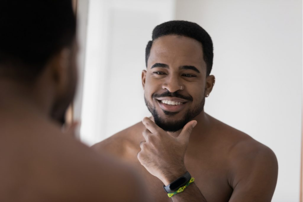 A man smiling and feeling good about himself while looking at the mirror. Positive self talk is great for the LGBTQ community.