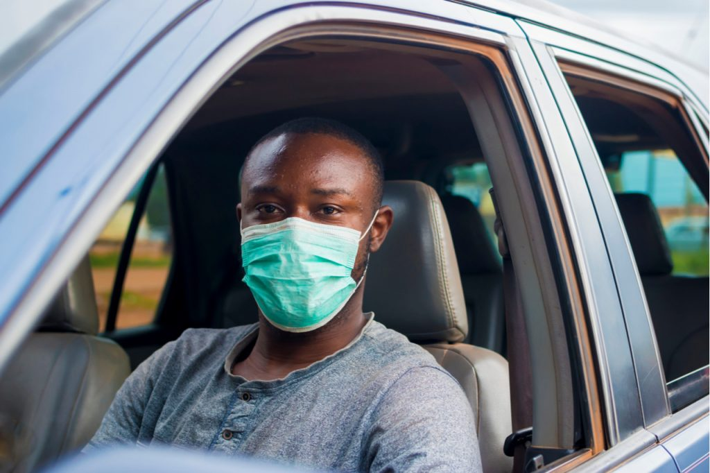 A man wearing a face mask for protection sitting at the driver seat of a car.