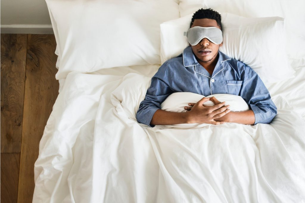 Man sleeping on white bed with his eyes covered.