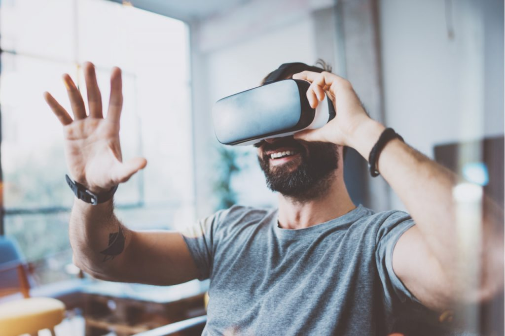 Man wearing a virtual reality glasses and he's having fun.