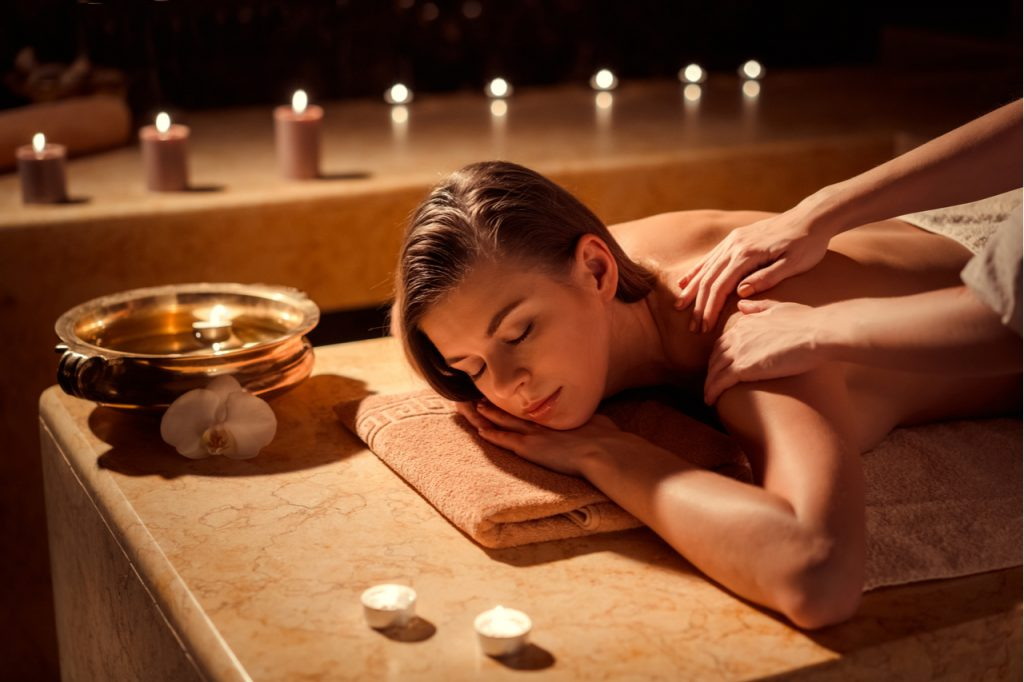 A woman having a back massage with candles for her to relax quickly.
