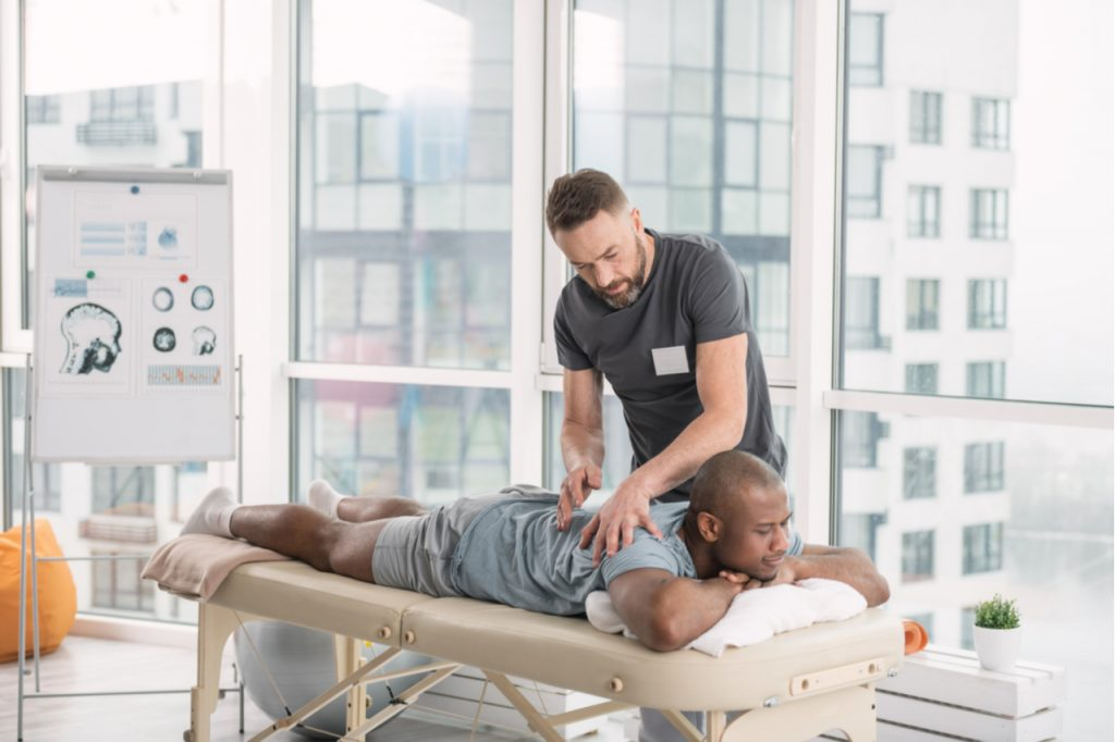 A male therapist doing a back massage to an African American man while explaining the benefits of massage therapy for athletes.