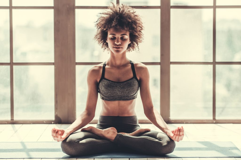 Woman in sportswear is meditating as part of her yoga journal.