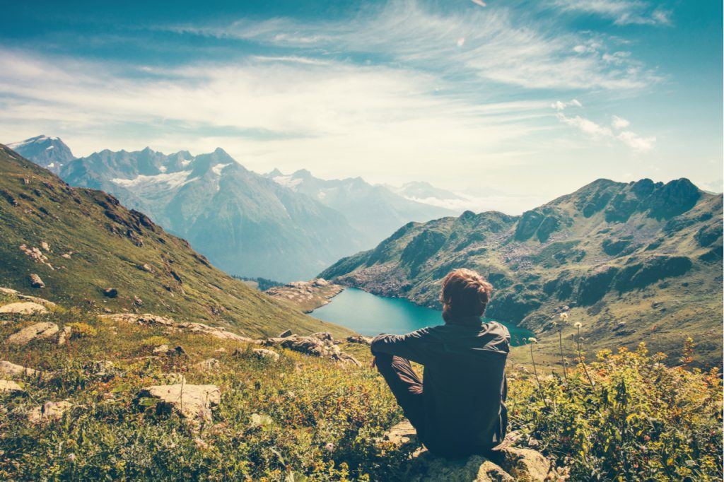 A man on top of a mountain looking at the lake as he goes nature bathing as his stress reducer.
