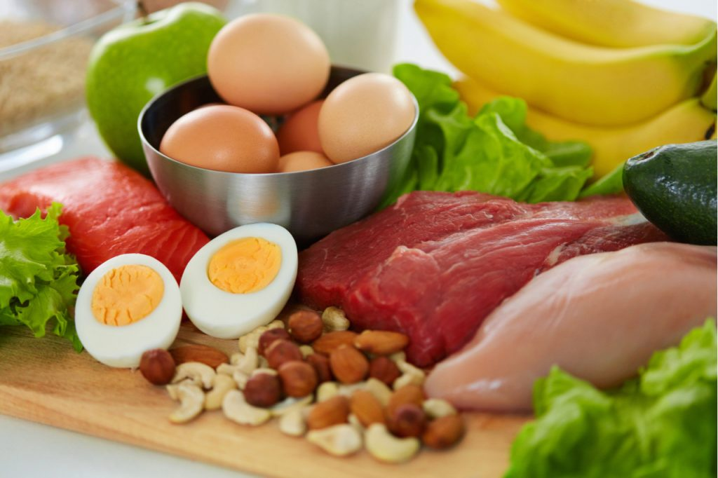 Fresh meat, salmon, hard boiled egg sliced into half, fresh eggs in a bowl, apple, bananas and nut in a wooden board are nutritious foods you need for fat loss workout.