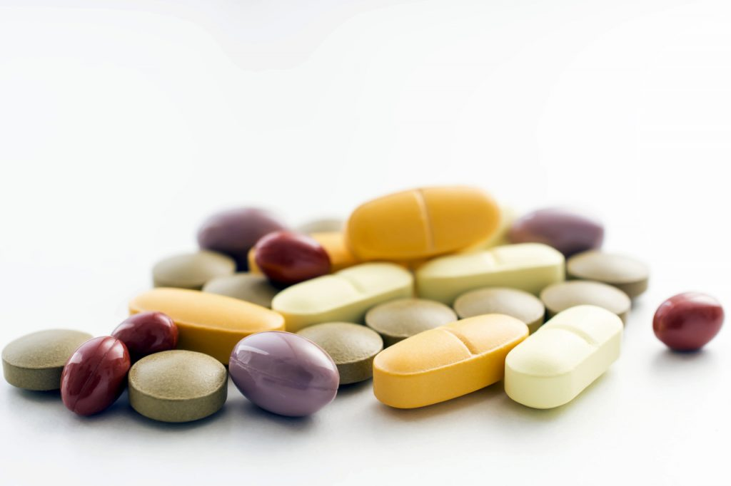 Vitamins and minerals pills on a white background.