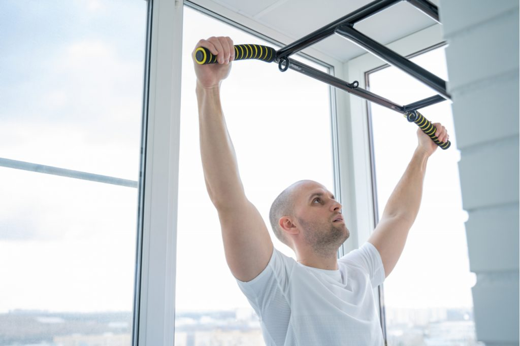 A man using a pull-up bar at home. A pull up bar is one of the best father's day wellness gifts.