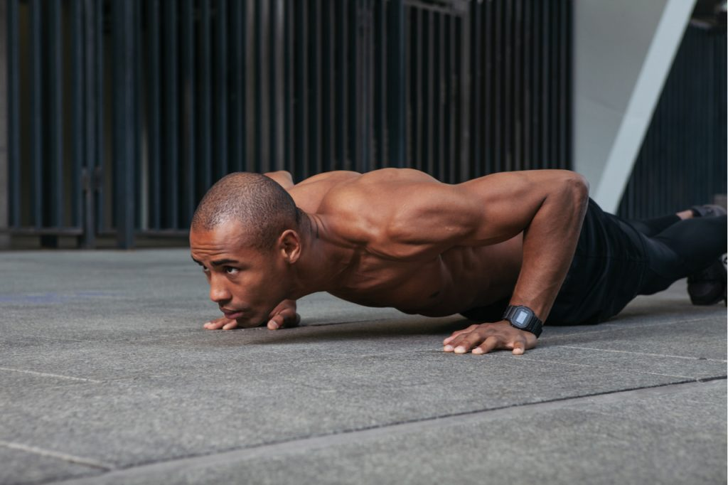 A fit Afro American man doing push-ups.