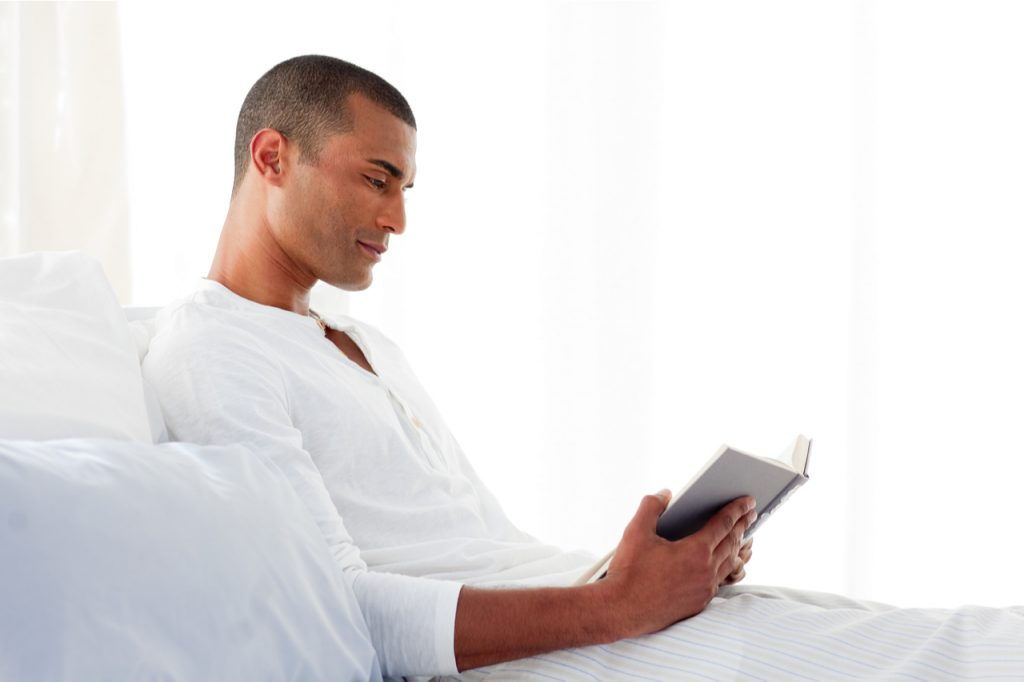 A man reading while lying on his bed.