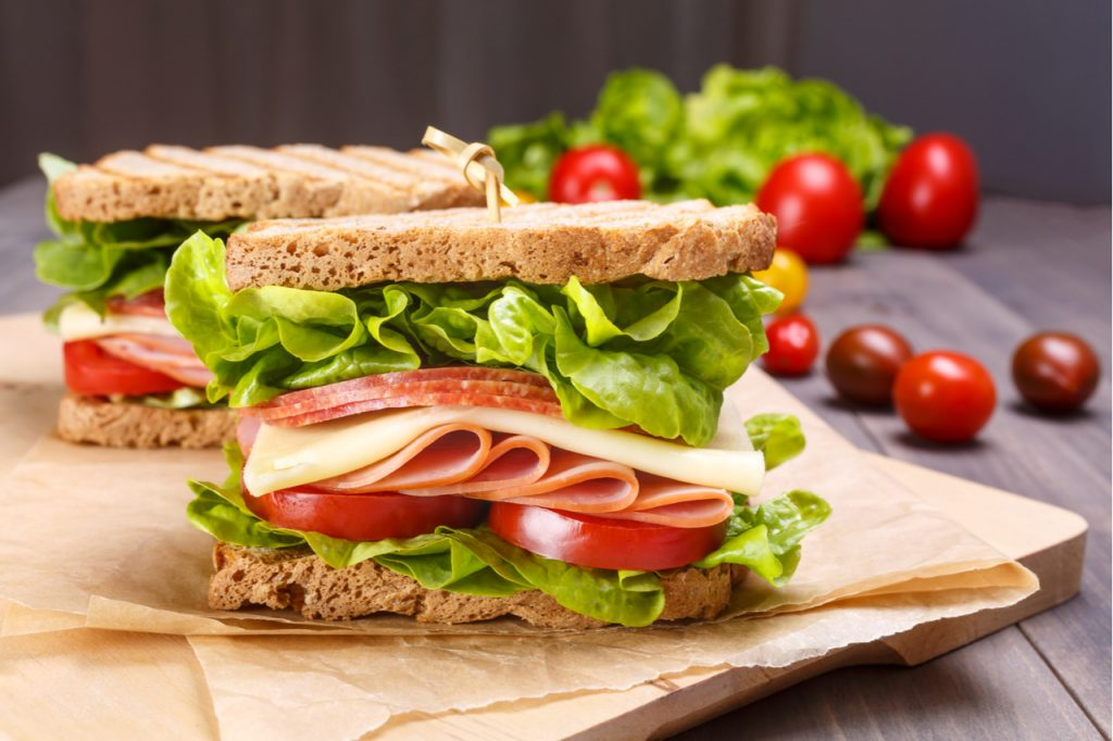 Sandwich with salami, cheese, tomatoes and greens.