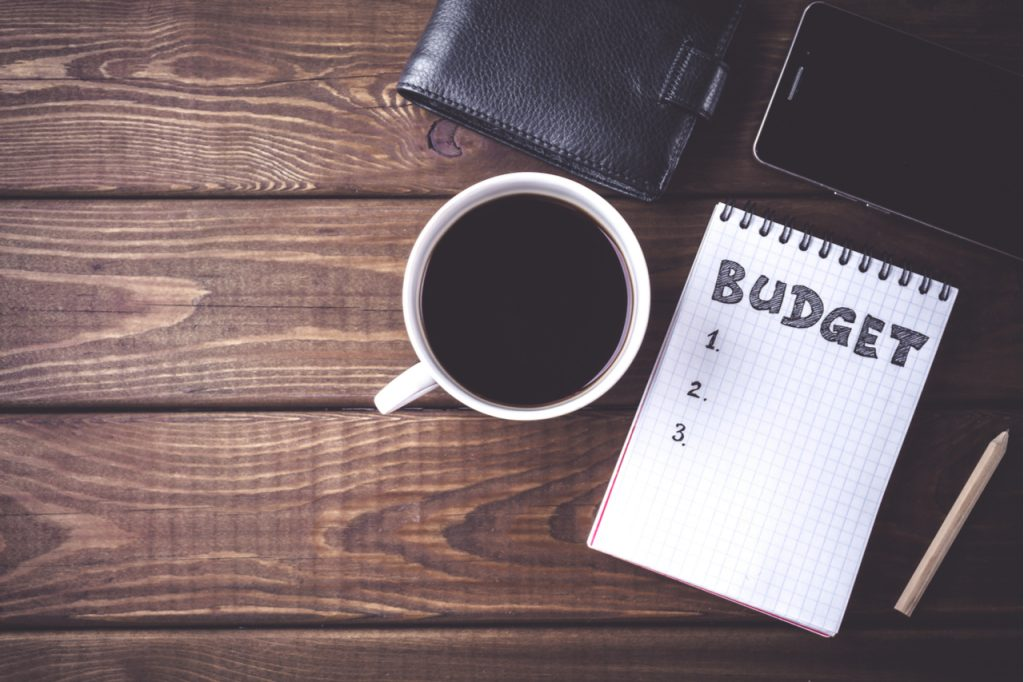 Top view of notepad with word Budget, mobile phone, cup of coffee, pouch on wooden background a start on how to save money.