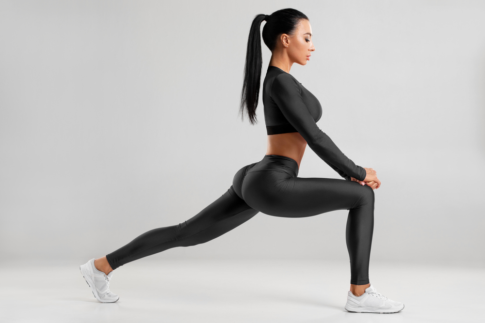 Fitness woman doing lunges exercises for leg muscle workout training.