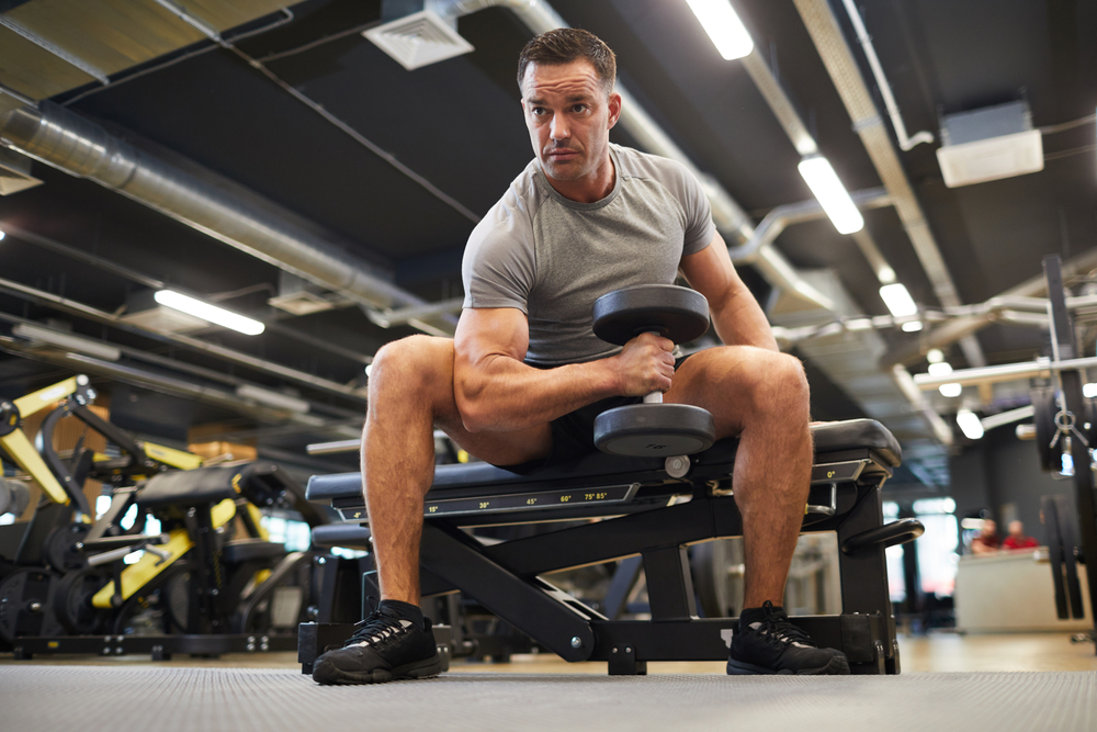 man doing exercises with dumbbells during strength workout in modern gym