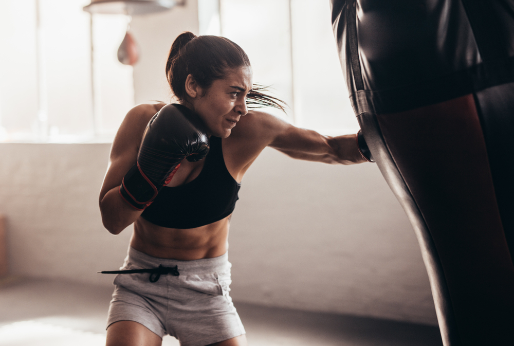 Fitness sporty woman working out on a punching bag.