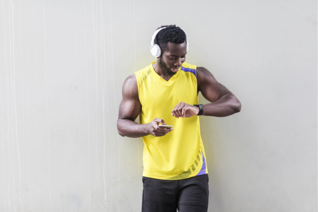 Sporty man holding smart phone and looking at smart watch.