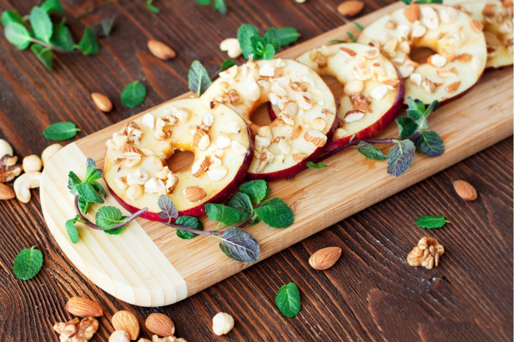 Slices of apples sprinkled with nuts and mint leaves on a wooden board.