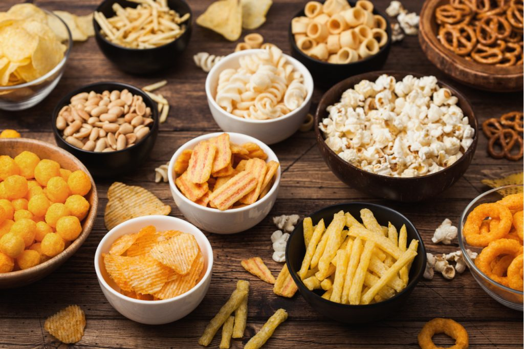 A variety of snacks in a bowl, like popcorn, nuts, pretzels, chips and fries to give you some snack ideas.