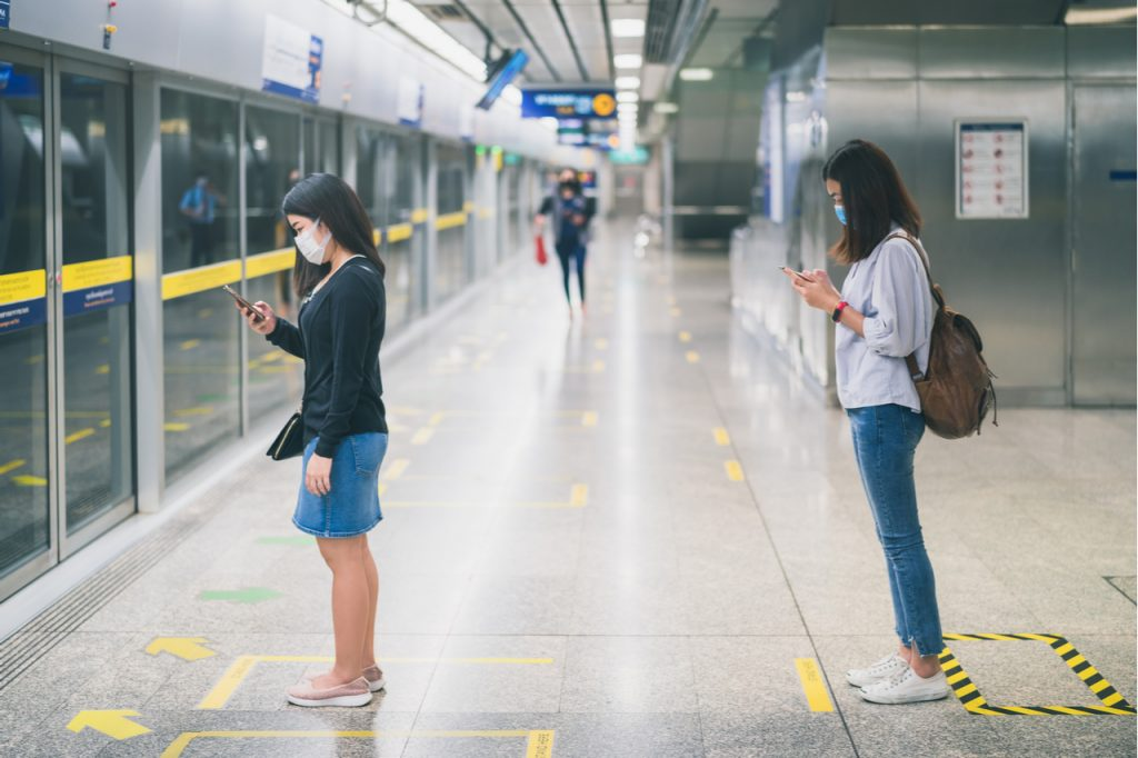 Two asian women wearing protective face mask practicing social distancing while in line waiting for the subway train.
