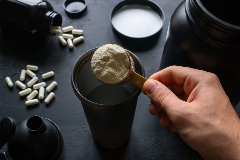Male athlete makes a creatine hcl cocktail in a black tumbler with tablets and jar in the background.