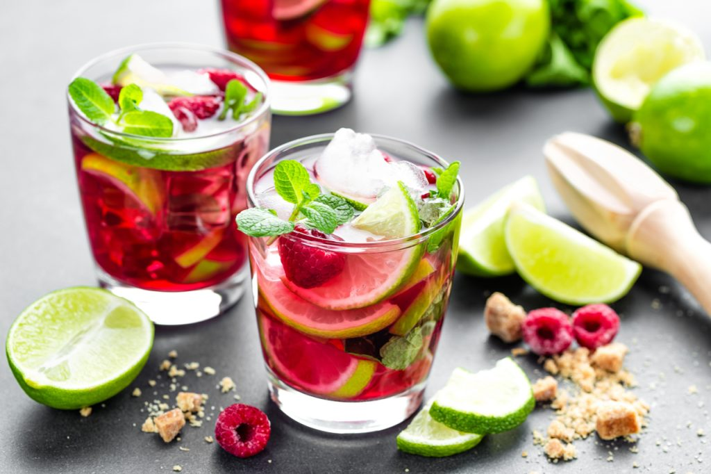 Raspberry cocktail with lime, mint and ice, cold, iced refreshing drink or beverage.