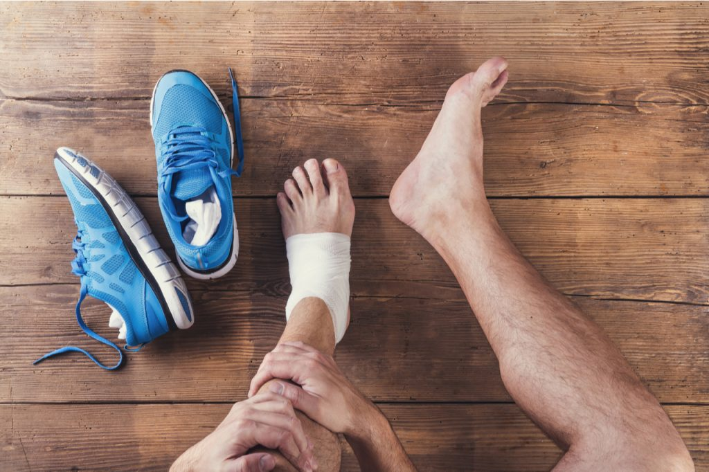 A man sitting on a wooden floor with bandage on his left foot because it was sprained and a pair of running shoes on the side. He is thinking what is good to treat sprain.