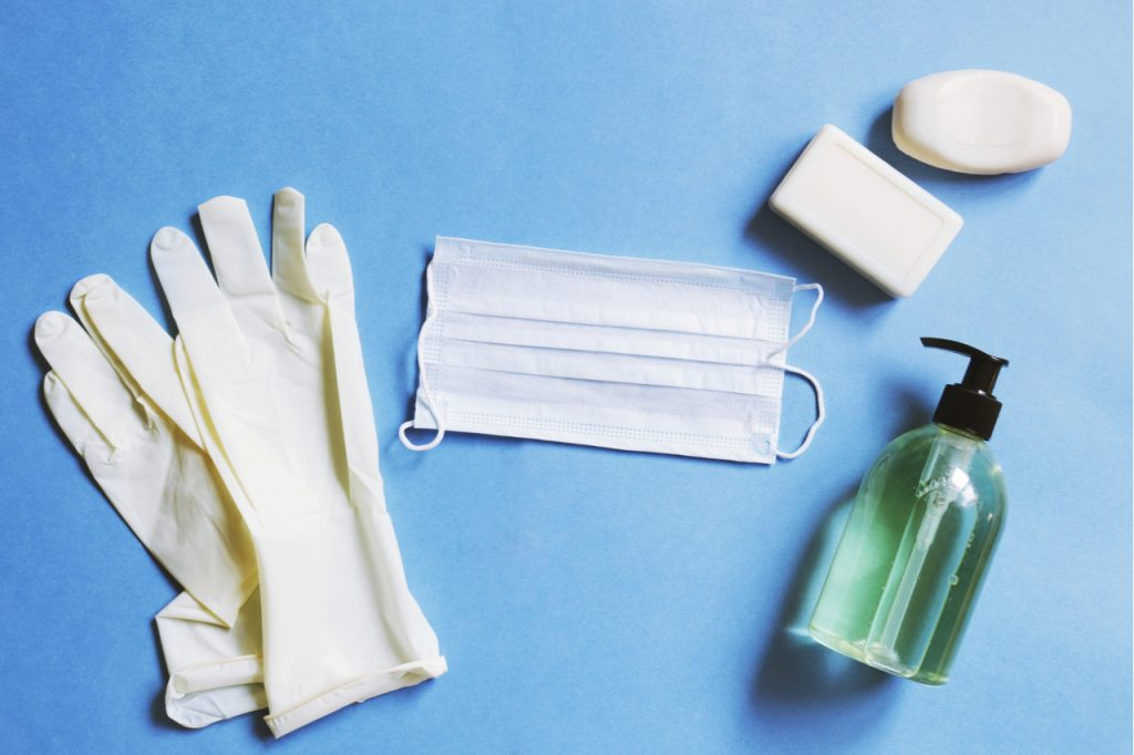 Latex gloves, medical mask, soap bar, sanitizer gel for home self-care ideas.