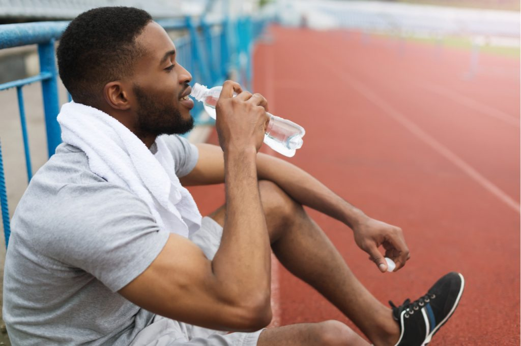 Athletic man resting after training on stadium, drinking water.