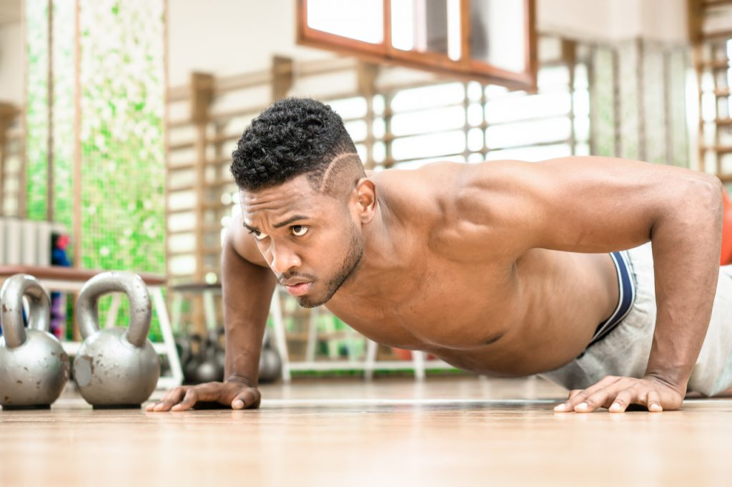 A man doing push up working on his bodyweight workout plan with serious facial expression inside gym.