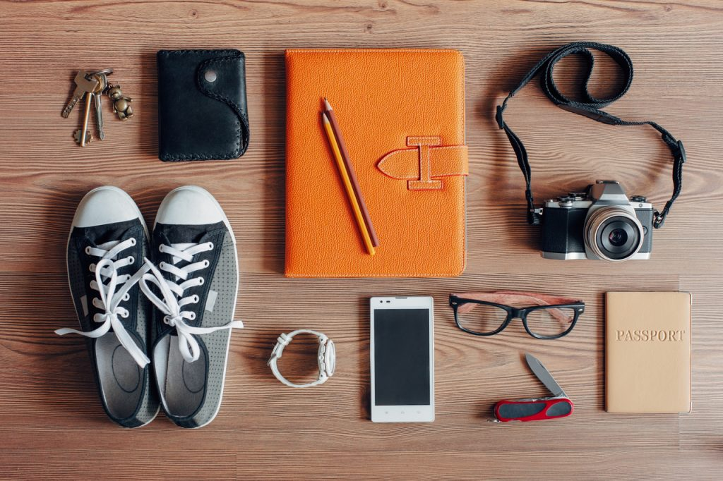 Travel essential items like a mobile phone, wallet, keys, passport, etc. on a wooden table. Make sure to follow save travel tips before and during your trip.