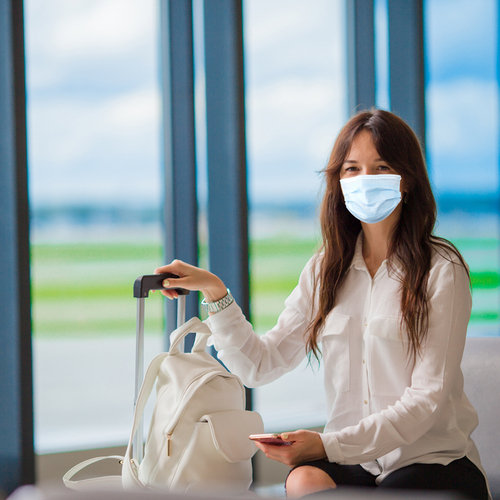A woman wearing protective face mask at the airport holding her luggage.