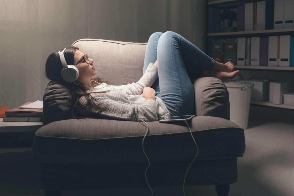 A young woman lying on an armchair with her headset on listening to music.